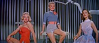 Monroe in How to Marry a Millionaire. She is wearing an orange swimsuit and is seated next to Betty Grable, who is wearing shorts and a shirt, and Lauren Bacall, who is wearing a blue dress.