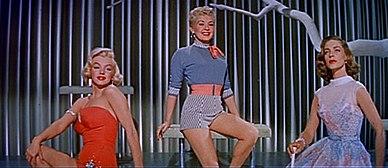 Monroe w How to Marry a Millionaire.  Ma na sobie pomarańczowy kostium kąpielowy i siedzi obok Betty Grable, która ma na sobie szorty i koszulę, oraz Lauren Bacall, która ma na sobie niebieską sukienkę.
