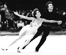 An ice dance couple performing a routine. The man, on the right, is dressed with a dark suit and holds his white-dressed partner by her waist and left hand.