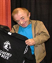 A short man in a jacket holding up a T-shirt to pose for a picture with it