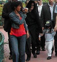 A group of adults and a child are shown in the photo. An African American female with short brown that is wearing a jean jacket and a light wash pair of jeans with a red shirt is seen holding a video camera, that is pointing forward. To the left of the female there is an opened black umbrella that is held above a Caucasian male with long black hair that is wearing all black clothes. In front of the male there is a child with black hair that is wearing a black cap with a blue shirt, a pair of white pants and black shoes. To the farthest left there ate two Caucasian males with dark brown hair. In the background, trees, bushes and people can be seen.