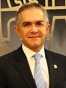 Miguel Ángel Mancera stands in front of a golden shield depicting an old Mexico City's shield. He looks directly to the camera and wears a black suit.