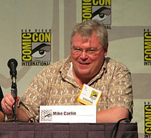 A man with white hair, glasses, and a brown shirt sits at a table with a microphone; a card in front of him reads