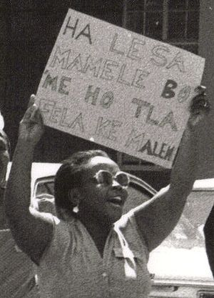 A Bosotho woman holding up a sign protesting v...