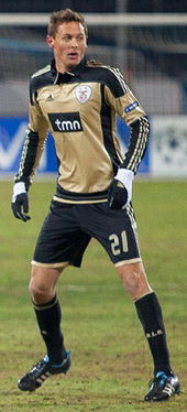 A young man on a football pitch during a game. He is wearing a bronze jersey with black details, and black shorts, socks and gloves