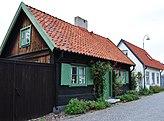 Fil:Norra murgatan 3 (tjärade trähuset) och 5 (vitputsade huset), Visby, Gotland.jpg