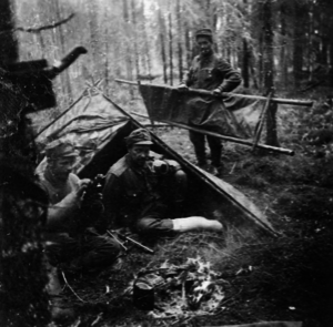 Operation Hokki - Image of the mission leader, Captain Ilmari Honkanen (center) who fell ill during the mission, so terribly that he was barely able to remain conscious by the time this image was taken. Rubber boots also made an abrasion to his foot which subsequently became badly infected and he was thus unable to return from the mission on foot and had to be secretly evacuated with a floatplane after the armistice was signed between Finland and the Soviet Union in September 1944. Image taken in either August of September 1944.
