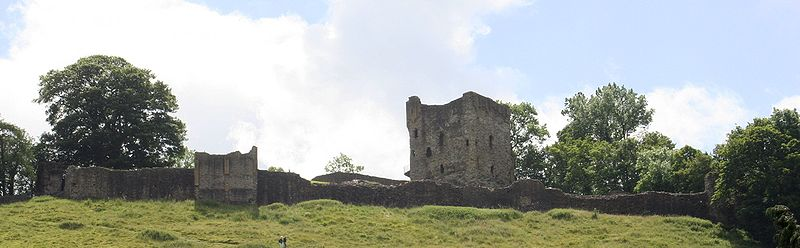 The remains of a low wall in front of a tall stone tower.