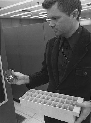 IBM 1360 - John Fletcher of Lawrence Livermore holds an IBM 1360 Photostore chip box in his right hand, and a loading tray in his left. The chip box holds 32 chips, the tray holds 33 boxes.