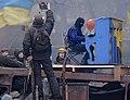 """Protester Piano Extremist plays on the roof burned """"Berkut"""" bus. The barricade across Hrushevskoho str. Kiev, 10.02.2014..jpg"""