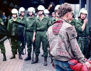Punk subculture - A punk faces a line of riot police at a 1984 protest in Germany