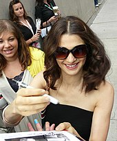 Weisz signing autographs for fans. She is wearing a black blouse and shades. Behind her there is a fan.