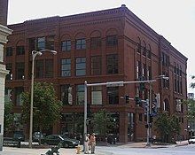 A large 4-story red brick building with many windows. The building is on a street corner with the front and one of the sides visible.