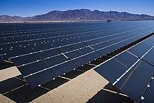 Bir kişinin boyunda yaklaşık 45 derece eğimli uzun koyu renkli panel sıraları, parlak güneş ışığında mesafeye kadar uzanır.