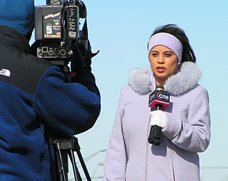 Journalist - A television reporter speaking into a microphone in front of a camera, 2005