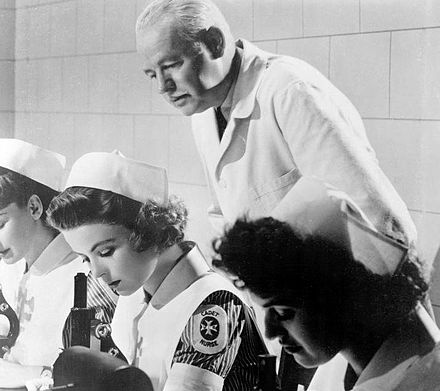 Cadet Nurse Peggy Adams (Dorothy McGuire) studies in the bacteriology laboratory in Reward Unlimited (1944), a promotional short film produced for the Public Health Service Reward-Unlimited-5.jpg