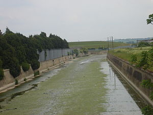 River Lee Diversion -  The river at Edmonton downstream of the confluence with the Overflow Channel. The grassed embankment of the William Girling Reservoir can be seen in the background