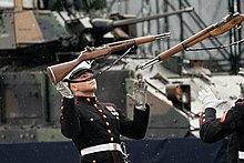 Two members of the United States Marine Corps Silent Drill Platoon get ready to catch their rifles which they have tossed up in the air.