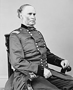 Black and white photo shows a man with a receding hairline and mutton chops. He is seated and wearing a dark uniform with two rows of buttons.