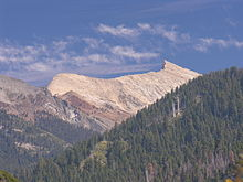 A light brown, almost white mountain rises above forested hills