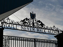 "Design of the top of a set of gates, with the sky visible. The inscription on the gates reads ""You'll Never Walk Alone""."
