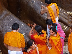 Jainism - Praying at the feet of a statue of Bahubali