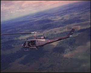 Side view of a Vietnamese Air Force UH-1H helicopter in flight over Southeast Asia. - NARA - 542344.tif