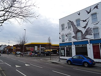 Alfred Hitchcock - Petrol station at the site of 517 High Road, Leytonstone, where Hitchcock was born; commemorative mural at nos. 527–533 (right).