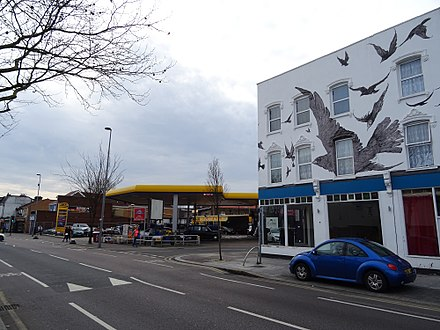 Petrol station at the site of 517 High Road, Leytonstone, where Hitchcock was born; commemorative mural at nos. 527-533 (right). Site of 517 High Road Leytonstone London E11 3EE (Birthplace of Alfred Hitchcock).jpg