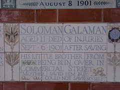 "A tablet formed of five tiles of varying sizes, bordered by yellow and blue flowers in an art nouveau style. The tablet reads ""Solomon Galaman, Aged 11 died of injuries, Sept 6 1901 after saving his little brother from being run over in Commercial Street, 'Mother I saved him but I could not save myself.'"""