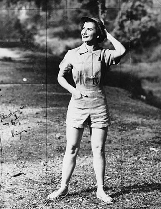Pantsuit - Young woman modelling a short pantsuit, Brisbane, 1952 The model wears a short-sleeved, collared blouse with front patch pockets, teamed with a pair of high-waisted, tailored shorts with slit pockets. She also wears a cloth hat and a pair of high-ankled sandals. This style is typical of the post-war period in women's clothing, when menswear style shirts, shorts and pants became popular in women's fashion.