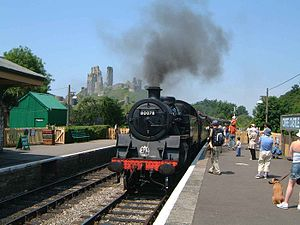 Swanage Railway - Steam loco 80078 pulls into Corfe Castle station. The castle is visible in the background.