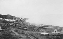 A beach crowded with military stores. Near the foreshore a plume of smoke rises