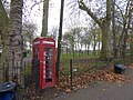Telephone box set into the railings of Queens Park (geograph 4752488).jpg