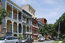 Rowhouses with arts-and-crafts styled porches (on both first and second floors) sit on a street across from a park.