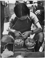 This Chinese woman does a thriving business in selling cigarette butts to the poor of Kunming. - NARA - 196232.tif