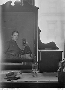 A dresser with a large mirror and a bottle of wine, a glass and some papers sitting on top. A man in military uniform can be seen in the mirror's reflection. He has his hand in his pocket, and is using a camera on a tripod.