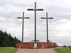 A memorial consisting of three crosses standing on a large brick pedestal. Each cross bears a name – Katyn, Kharkiv, or Mednoye.