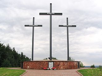 A Memorial consisting o three crosses staundin on a lairge brick pedestal. Each cross bears a name - Katyn, Kharkiv, or Mednoye.