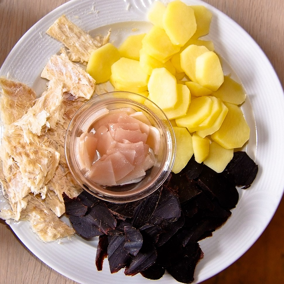 The whale meat is dark purple and shredded like jerky, the blubber is a pale-pink color and in slices, the dried fish is a light-brown color and ripped into slices, and the potatoes are light-yellow and cut into thin slices.