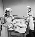 Two Wren cooks carve ham for the lunchtime meal in the galley of a Fleet Air Arm base in Scotland, 1943. D13387.jpg
