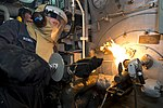 U.S. Navy Petty Officer 3rd Class Alexander Wendell inserts a torch into a boiler during a manual boiler check aboard the amphibious dock landing ship USS Carter Hall (LSD 50) as the ship operates in the Persia 130708-N-NB538-105.jpg