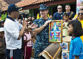 U.S. Navy Rear Adm. Tilghman D. Payne, center, the commander of Joint Region Marianas, holds a painting presented to him by an elementary school student during a community service event for exercise Cooperation 130522-N-IY633-580.jpg