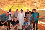 U.S. Sailors assigned to the guided missile destroyer USS Higgins (DDG 76) pose for a photo with Adel Sultan, center, the vice president of Bahrain Mobility International, during a community relations event 130617-N-UP025-002.jpg