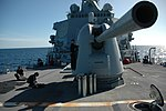 U.S. Sailors assigned to the weapons department on the guided missile destroyer USS Curtis Wilbur (DDG 54) position the ship's Mk 45 lightweight gun and clear the deck after a live-fire exercise during 130608-N-AX577-256.jpg