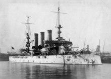 Um navio de guerra branco com três chaminés e dois mastros altos no porto.