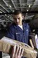 US Navy 030505-N-0413R-001 Storekeeper Seaman Alfredo Arreola helps sort and distribute incoming mail in the hanger bay aboard USS Nimitz (CVN 68).jpg