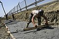 US Navy 040723-N-5821W-013 Builder 3rd Class Craig Miller assigned to Naval Mobile Construction Battalion Seven Four (NMCB 74), smoothes out freshly poured concrete at a construction site aboard the naval station.jpg