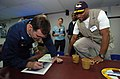 US Navy 050212-N-8629M-142 Commanding Officer, Medical Treatment Facility, Capt. David Llewellyn, signs a photograph of the Military Sealift Command (MSC) hospital ship USNS Mercy (T-AH 19) for New York Giants wide receiver Ama.jpg