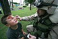 US Navy 050802-N-1113S-001 Chief Master-at-Arms Joseph Mortimer paints the face of a five-year-old with a camouflaged paint during the 22nd Annual Naval Air Facility (NAF) Atsugi National Night Out.jpg